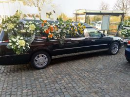 Corbillard Cadillac noir devant église vu du coté droit